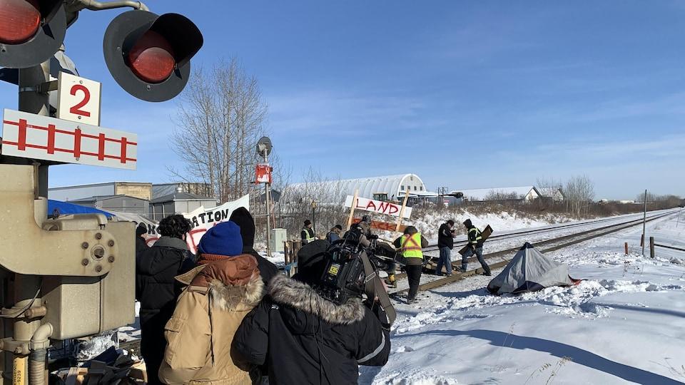 Des contre-manifestants retirent des palettes en bois de la voie ferrée.
