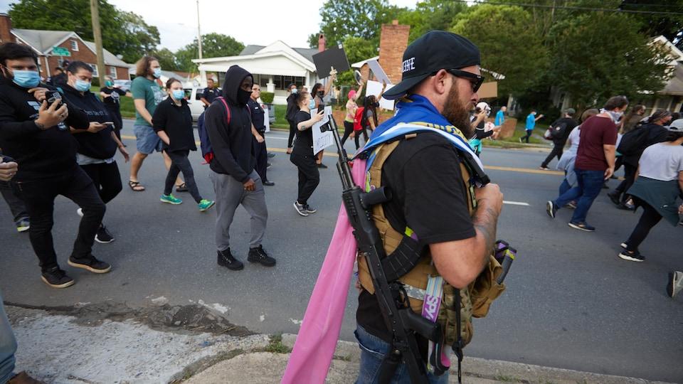 Un homme armé d'un fusil se promène en périphérie d'une manifestation antiraciste.