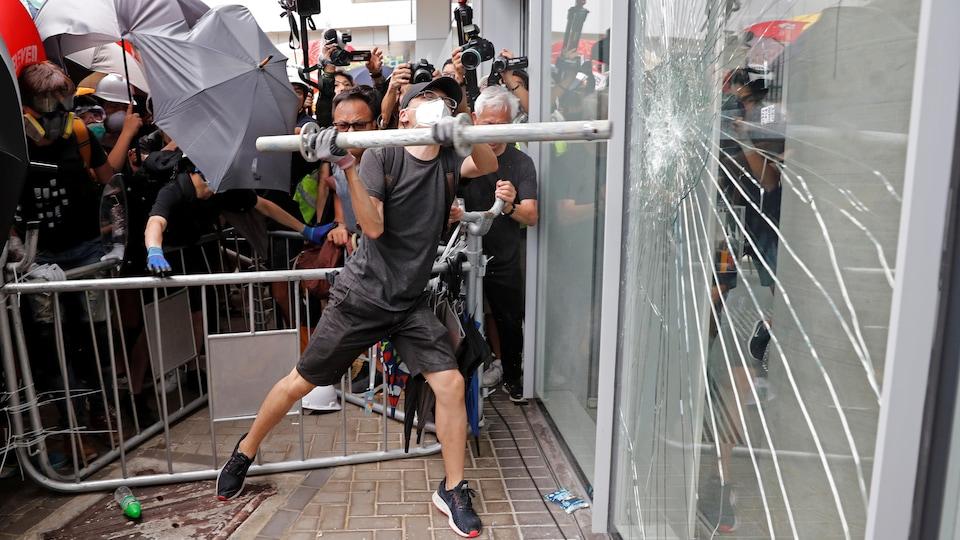 Un homme masqué s'efforce de briser une fenêtre d'un bâtiment à l'aide d'une barre de fer. Autour de lui, une foule composée de manifestants, de photographes et d'agents de sécurité se masse derrière des barrières.