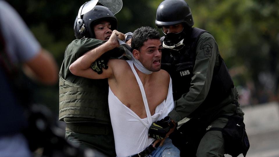 Deux policiers tentent de maîtriser un manifestant, à Caracas le 27 juillet 2017