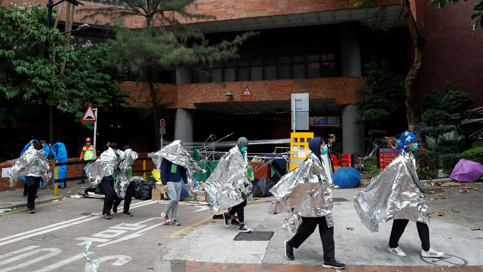 Des manifestants se rendent aux policiers.