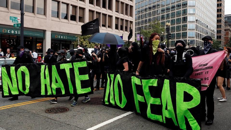 Des contre-manifestants dans les rues de Washington brandissant de grandes banderoles horizontales sur lesquelles est inscrit «pas de haine, pas de peur».