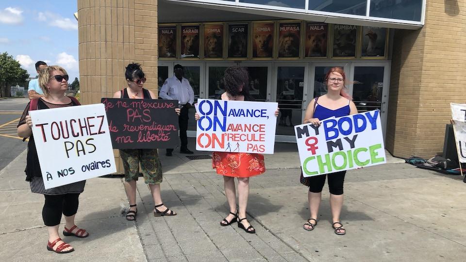 Quatre manifestantes portent des pancartes devant le cinéma. On peut notamment y lire « Touchez pas à nos ovaires ».