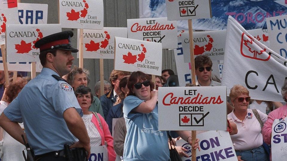Des manifestants brandissent des pancartes sur lesquelles il est écrit en anglais « Ne nous enlevez pas notre Canada » et « Laissez les Canadiens décider ». Un policier se tient à côté d'eux.