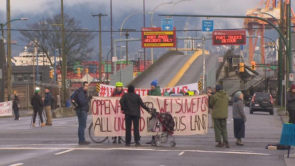 Une dizaine de manifestants rassemblés sur Clark Drive autour d'une banderole bloquent l'entrée au port de Vancouver.