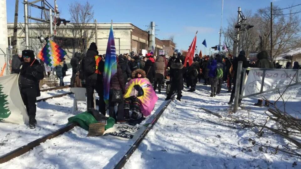 Des manifestants sont rassemblés sur des voies ferrées enneigées avec des drapeaux et des pancartes.