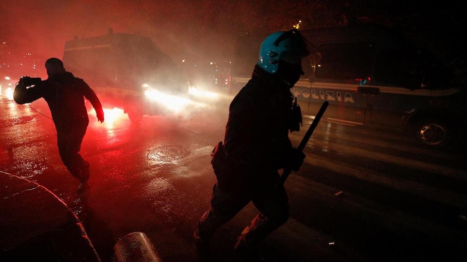 Des gens se déplacent dans la noirceur d'une rue, dont un policier en uniforme, matraque à la main.