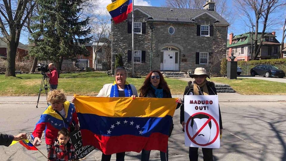 Des manifestants anti-Maduro tiennent des drapeaux devant l'ambassade du Venezuela à Ottawa.