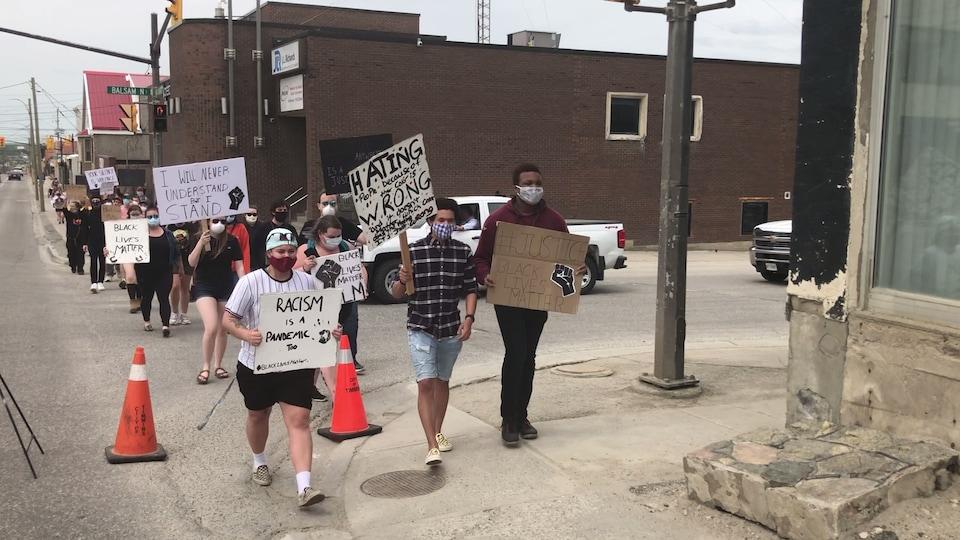Des manifestants marchent sur un trottoir.