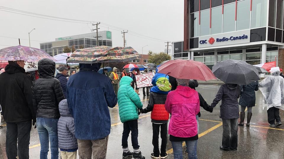 Il pleut et les gens s'abritent sous leur parapluie.