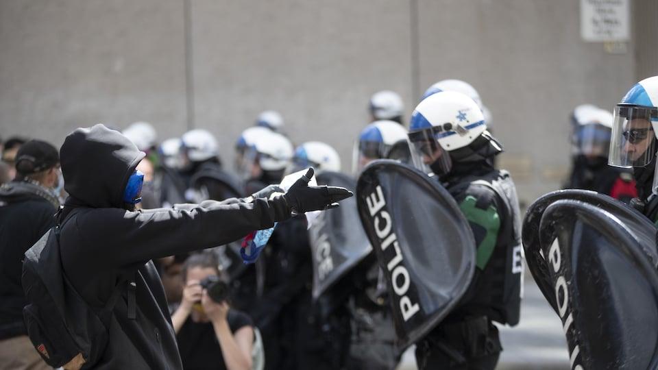 Des policiers munis de casques et de boucliers devant des manifestants.