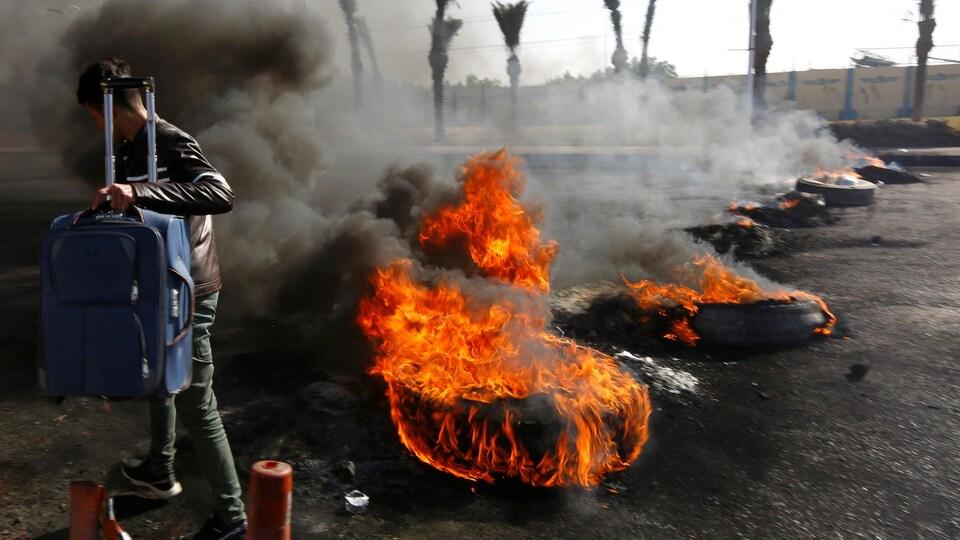Des pneus brûlent sur une route et un homme transporte une valise.