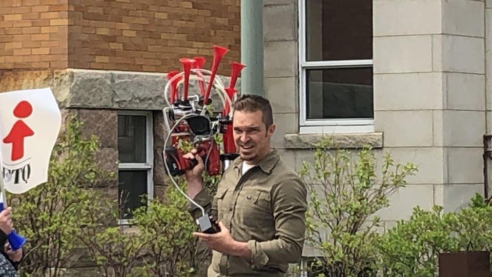 Un homme avec un appareil qui imite le son des klaxons dans les mains.