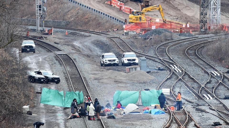 Une dizaine de personnes sont assises près de tentes installées sur les rails.