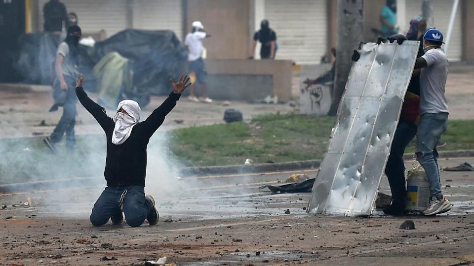 Des manifestants se cachent derrière une plaque en acier portant des traces de balle, tandis qu'un autre, le visage couvert d'un foulard, est à genoux, bras levés.