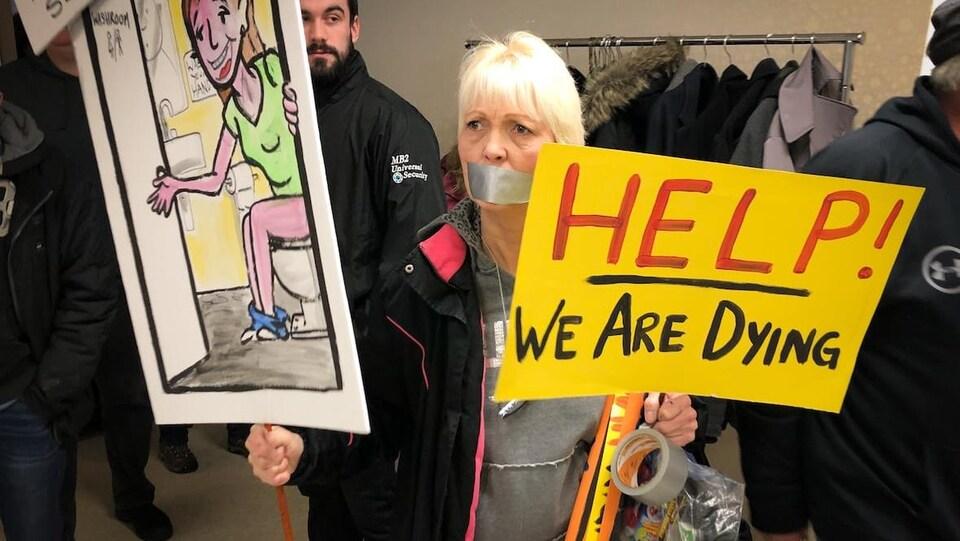Une manifestante porte une pancarte où il est écrit : «À l'aide, nous sommes en train de mourir.»