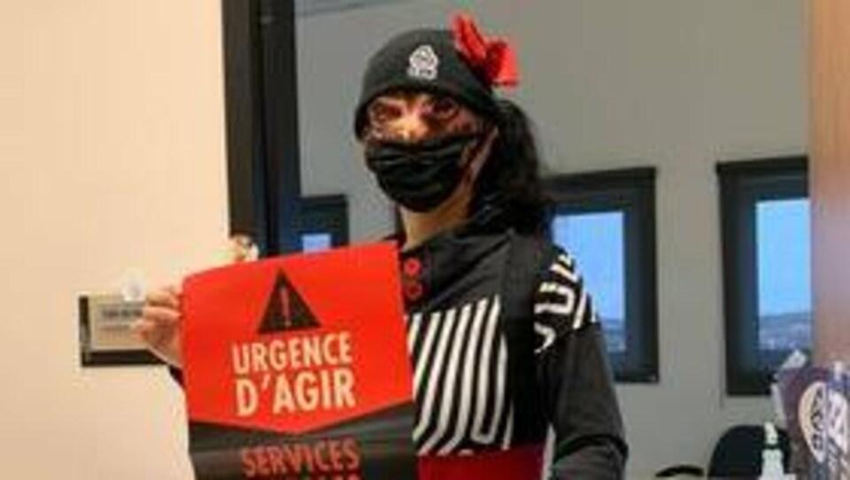 """Une manifestante déguisée tenant une pancarte revendicatrice. On peut y lire: """"urgence d'agir. Services publics à rebâtir."""""""