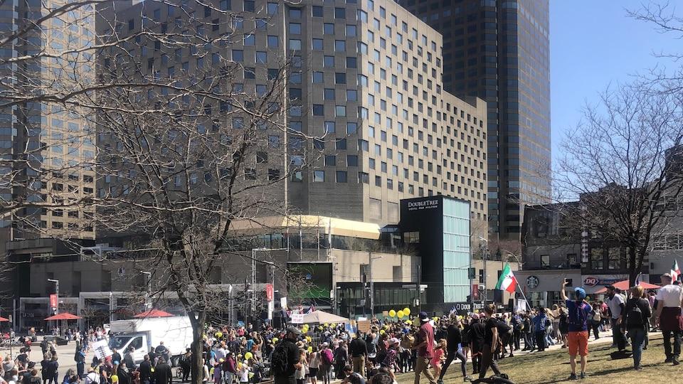 Des dizaines de personnes sont rassemblées au centre-ville, près d'une aire gazonnée.