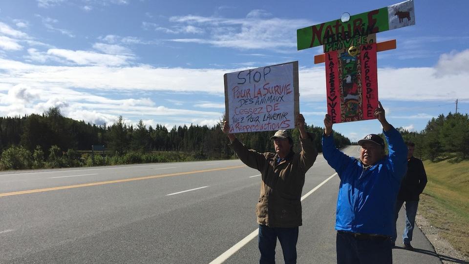 Deux manifestants au bord de l'autoroute tiennent en haut de leur tête des pancartes qui demandent la protection de la nature et des orignaux.