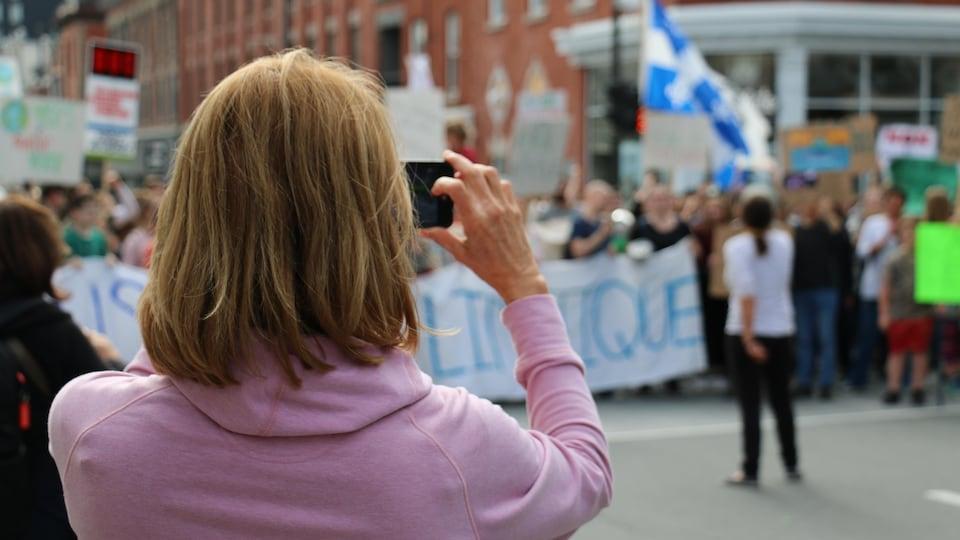 Une femme tenant un téléphone cellulaire.