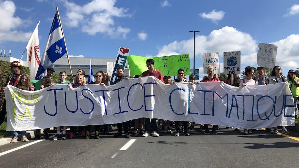 Des manifestants tenant une bannière.