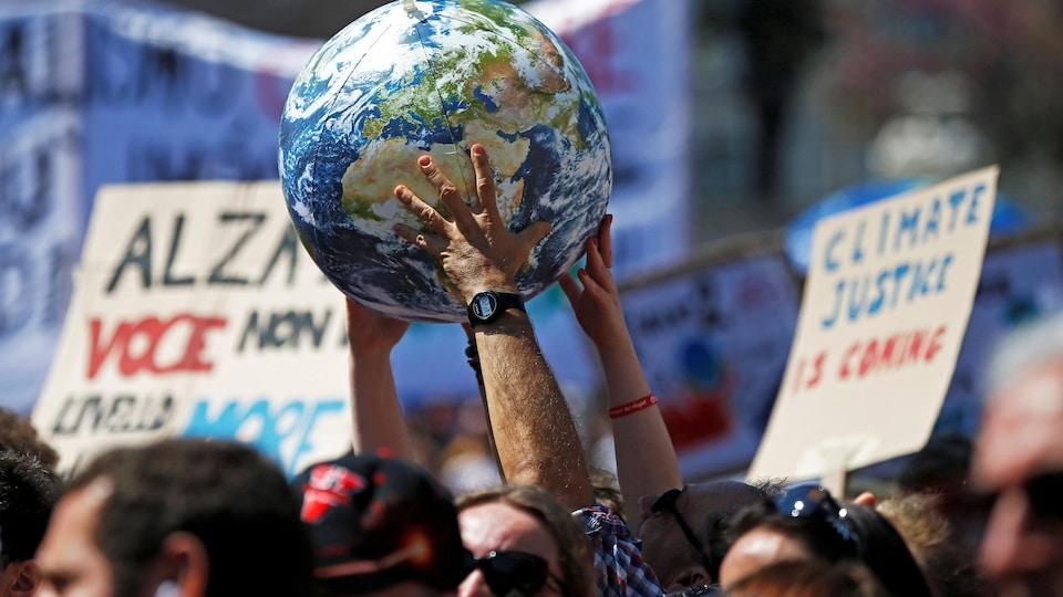 Des gens manifestent et tiennent une planète.