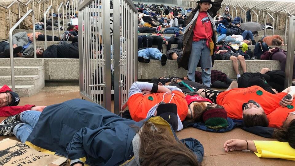 Des jeunes sont allongés sur les marche du Musée canadien pour les droits de la personne.