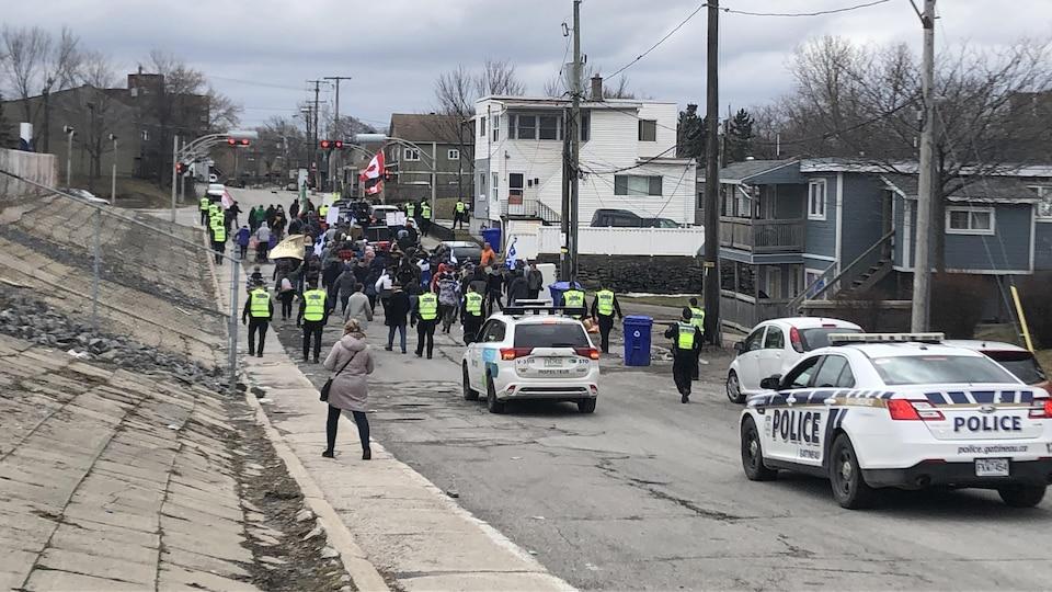 Des citoyens défilent dans une rue de Gatineau et des policiers surveillent le déroulement de la manifestation.