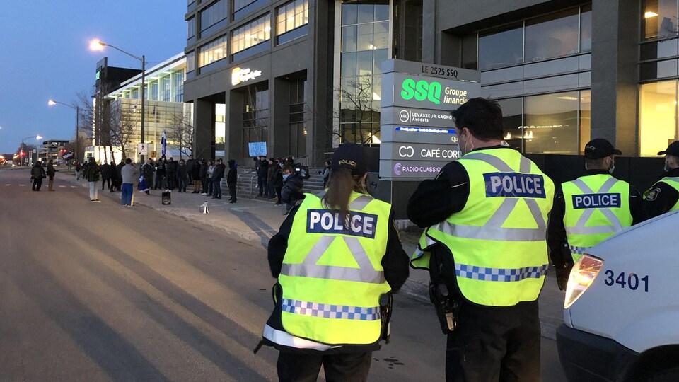 Des policiers dans une rue à Québec et des manifestants au loin.