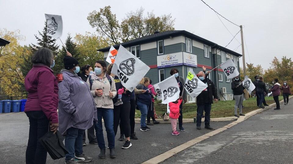 Un groupe de manifestant avec des affiches syndicales en main, devant un centre de la petite enfance.