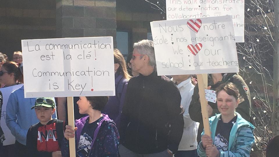 Des enfants et des adultes devant l'École du Sommet, brandissant des pancartes sur lesquelles est écrit : «La communication est la clé!» et «Nous aimons notre école et nos enseignants»