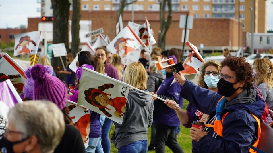 Éducatrices avec des pancartes sur le bord du boulevard René-Lepage à Rimouski.