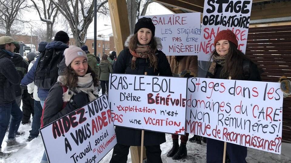 Trois étudiantes font la pose avec des pancartes qui dénoncent la non rémunération des stages.