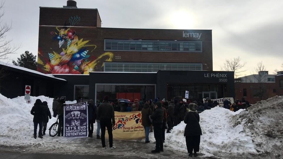 Un groupe de personnes devant une bâtisse sur laquelle on peut lire le nom du cabinet d'architectes Lemay.
