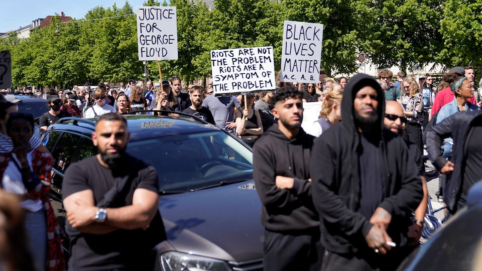 Des manifestants sont massés, certains tenant des pancartes avec des slogans réclamant plus de justice sociale.