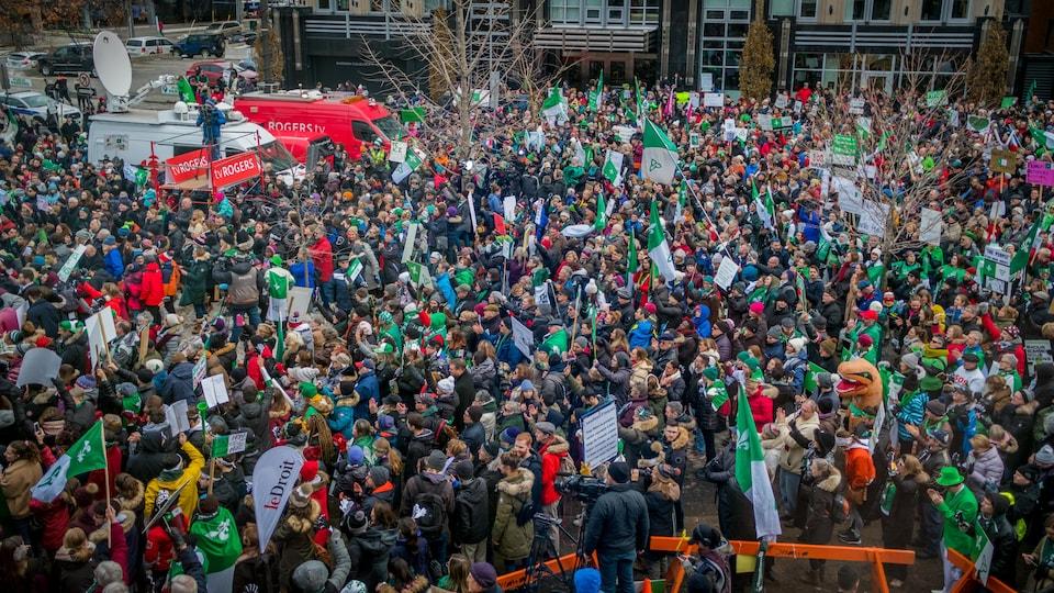 La vue en hauteur d'une foule de manifestants tenant des drapeaux verts et blancs.