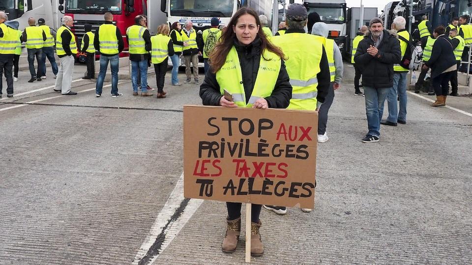Une femme tient une pancarte «stop aux privilèges, les taxes tu allèges.»