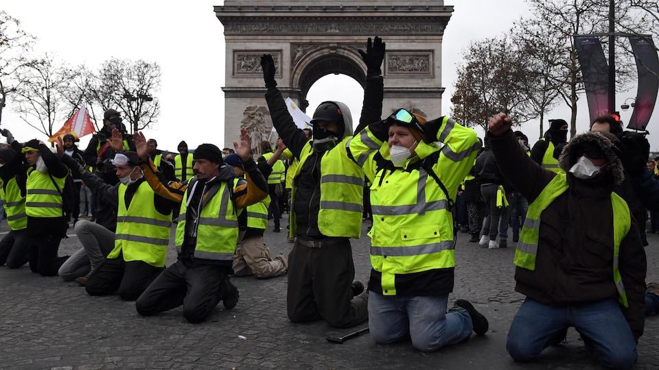 Des hommes en gilets jaune à genoux.