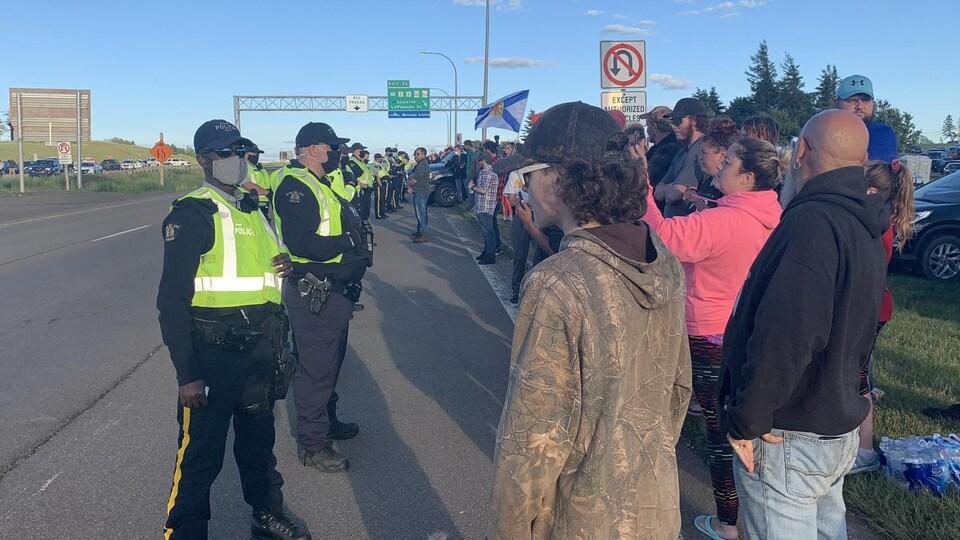 De nombreux policiers tentent de disperser les manifestants qui bloquent l'autoroute entre le Nouveau-Brunswick et la Nouvelle-Écosse, mercredi soir.