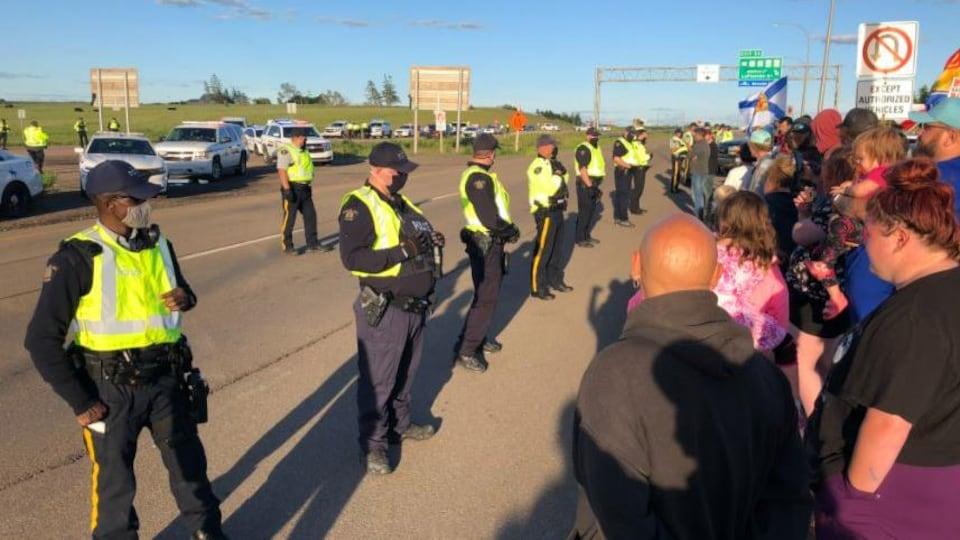 De nombreux policiers tentent de disperser les manifestants qui bloquent l'autoroute entre le Nouveau-Brunswick et la Nouvelle-Écosse.