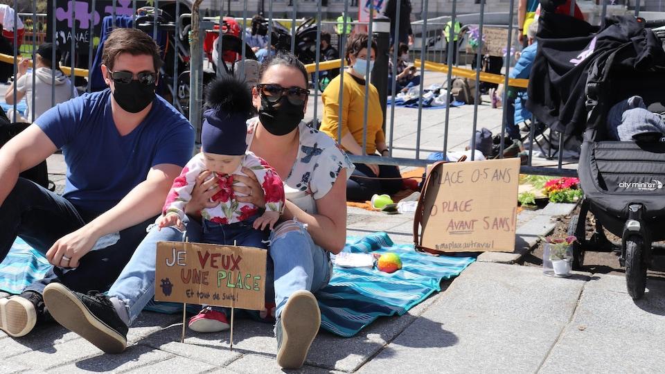 Un couple assis. La mère tient son enfant dans ses bras au milieu d'un sit-in, devant l'Assemblée nationale