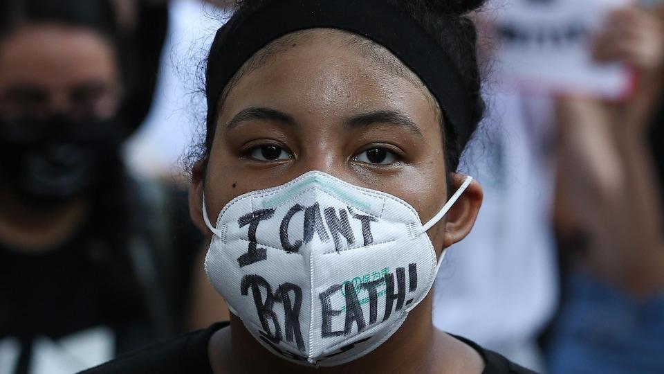 Une jeune femme noire portant un masque.