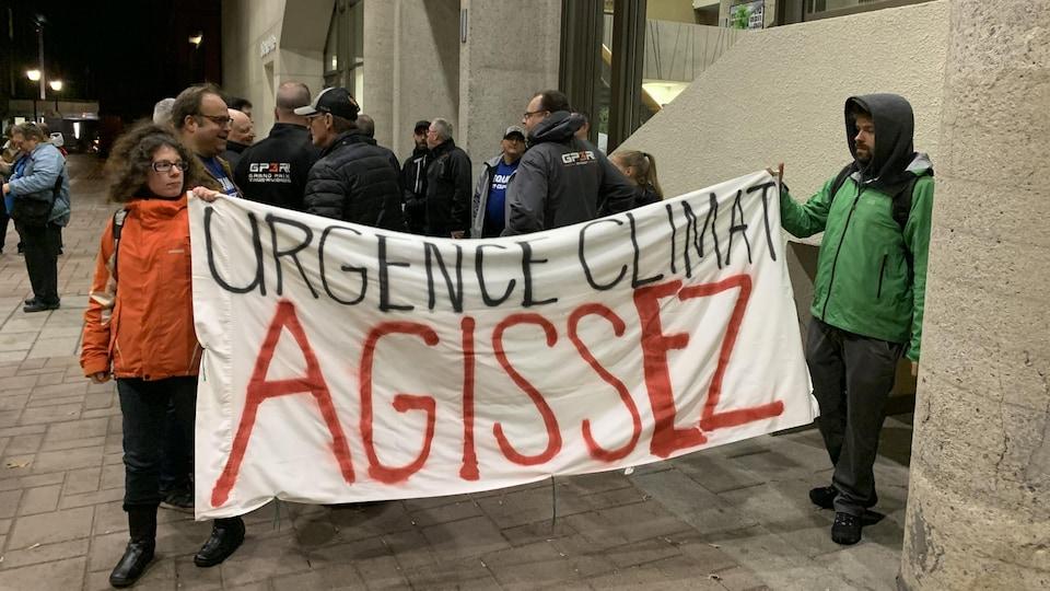 Une banderole qui dit Urgence climat agissez, devant des gens associés au Grand Prix de Trois-Rivières.