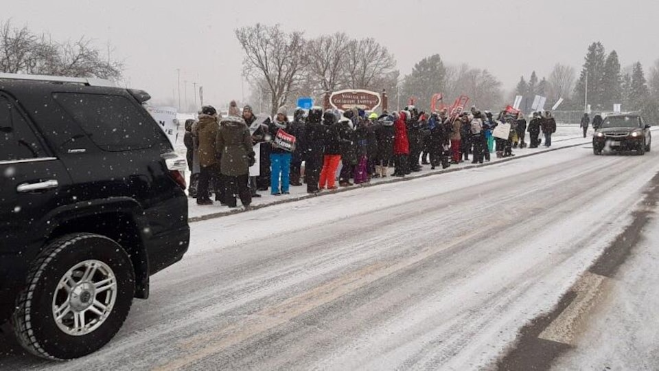 Un groupe de manifestants avec des pancartes sur le trottoir en hiver.