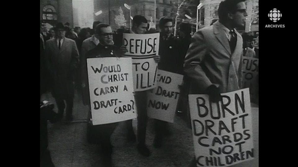 Jeunes hommes qui tiennent des pancartes qui dénoncent la conscription et la guerre du Vietnam.