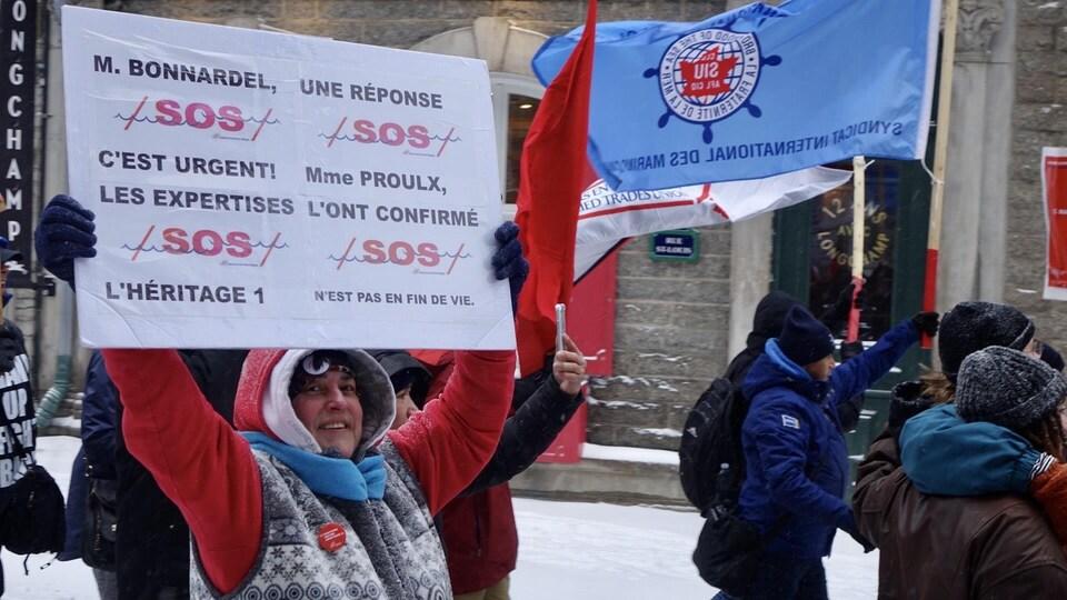 Des manifestants brandissent des pancartes demandant au gouvernement d'aider à la préservation du traversier.