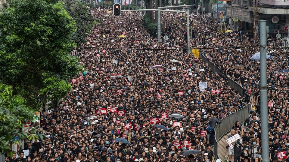 Une foule monstre remplit une grande artère de Hong Kong.