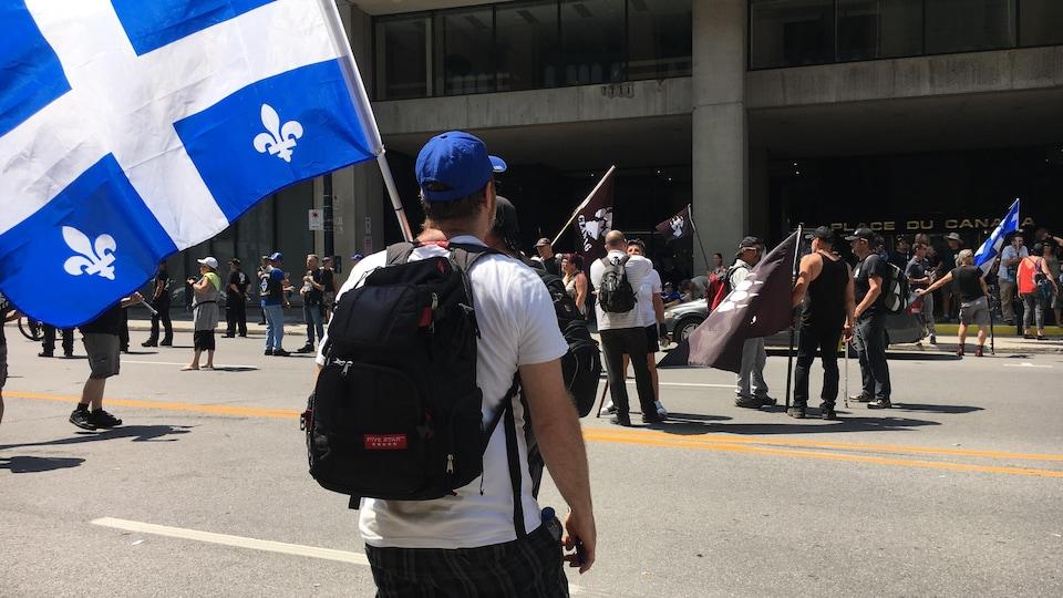Des membres du groupe Independance Day ont brandi des drapeaux du Québec à la Place du Canada devant les bureaux d'immigration pour dénoncer «l'immigration illégale» au Canada.