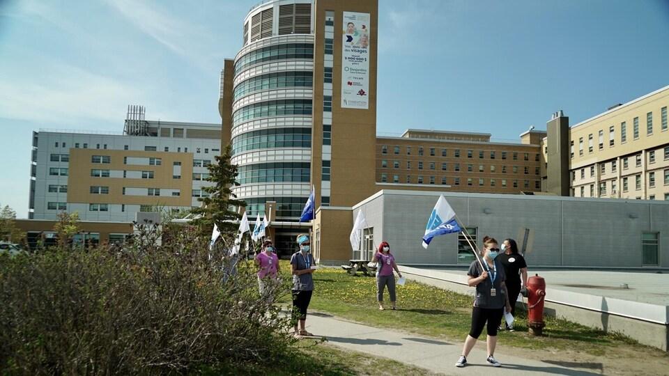 Des manifestants brandissent des drapeaux devant l'Hôpital de Rimouski.