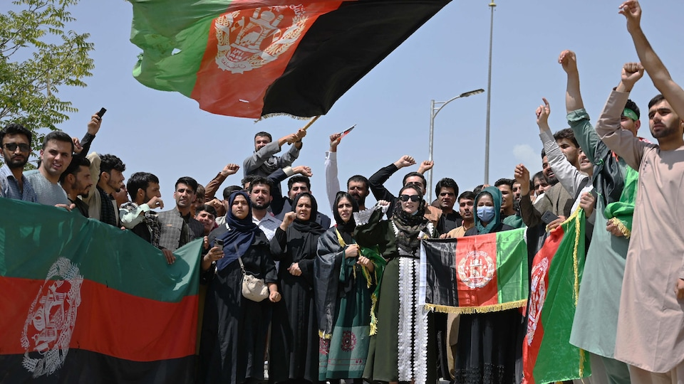 Varias personas, incluidas mujeres, ondean banderas.  Muchos de ellos tienen un puño en el aire.